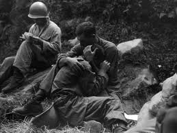 A soldier comforts another in the midst of war.